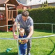 Father and son when installing large garden trampo...