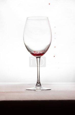 Photo pour Un verre de vin avec un peu de vin et quelques gouttes de rouge à l'extérieur. Buvez - image libre de droit