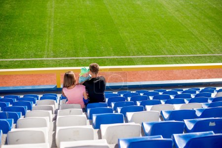 family sitting in the football grandstand