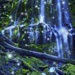 Magical waterfall with fairies and blue misty wate...