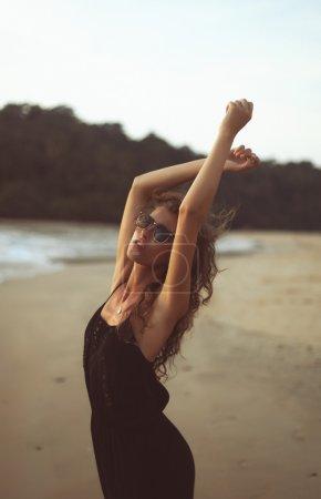Photo pour Portrait d'une jeune belle femme aux longs cheveux bouclés au bord de la mer sous le coucher du soleil du soir - image libre de droit