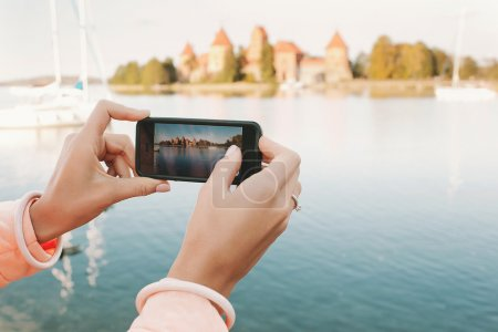 Woman hands with phone taking picture of historical place