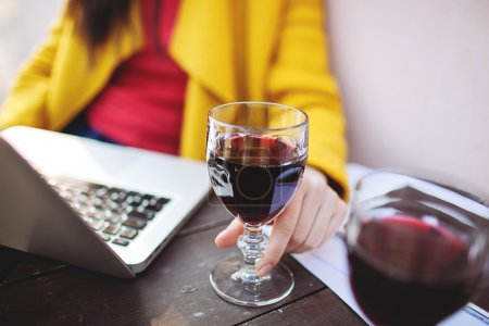 Woman holds red wine tablet and laptop in street cafe