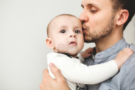 Happy father kissing baby in hands with isolated background