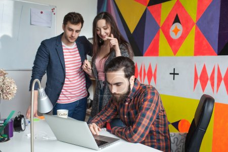 Photo for Start-up team of three young hipster guys in modern office collaborating - Royalty Free Image