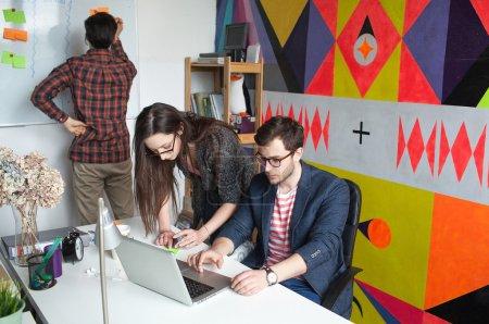 Photo pour Une équipe de start-up de trois jeunes hipsters dans un bureau moderne collaborant - image libre de droit