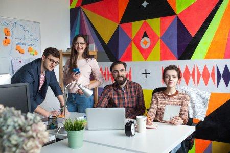 Photo pour Une équipe de quatre jeunes collègues créatifs discutant du travail dans un bureau moderne - image libre de droit