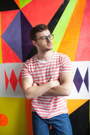Hipster male in modern office hands crossed on his chest