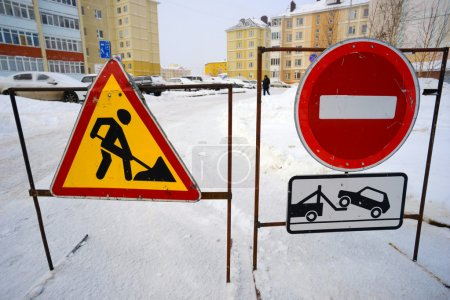 Road signs prohibiting passage when clearing snow in  yards.