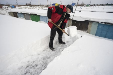 Clearing snow from  roof of the garage.