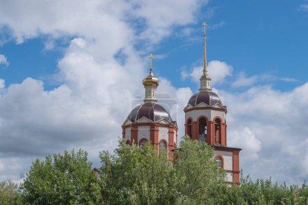 Parte superior de marrón y beige Iglesia Ortodoxa de Presentación del Señor con campanario y aguja, cúpula redonda y cruces ortodoxas doradas, detrás del follaje verde de los árboles. KALINININGRAD, RUSIA, 13 DE JULIO DE 2020