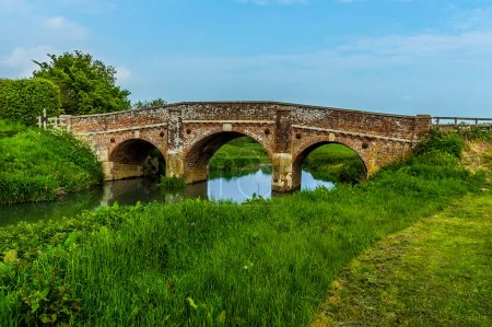 Photo for A view along the banks of the River Rother towards the old bridge at Bodiam, Sussex in springtime - Royalty Free Image