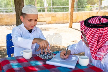Photo for Two arabic boys discussing some project - Royalty Free Image