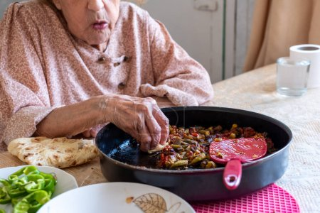 Photo for Old woman enjoying some homemade okra - Royalty Free Image