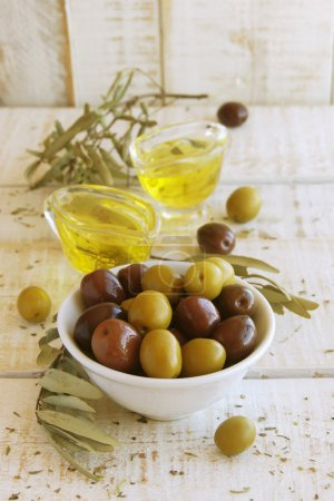 Black and green olives, olive oil on a white wooden table