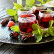 Berry juice in a glass with berries, ice and mint,...