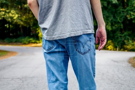 Photo for Teen boy standing at a fork in the road and thinking about his life choices - Royalty Free Image