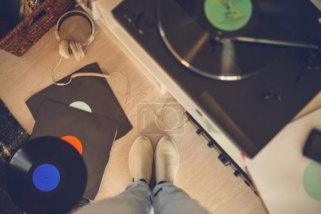 Female legs among vinyl records and gramophone