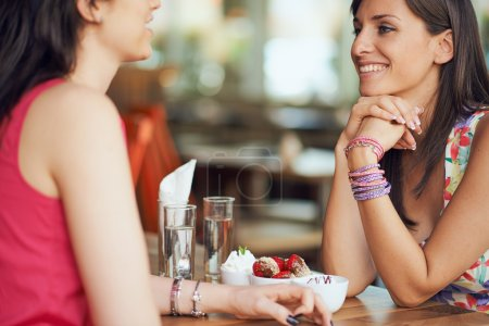 Two girls in a coffee shop, smiling, gossiping, dr...