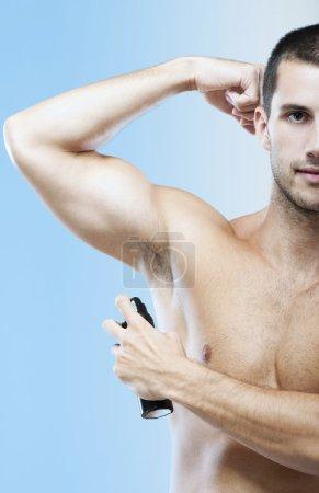 Photo pour Photo d'un bel homme utilisant du déodorant. Homme utilisant un déodorant - image libre de droit