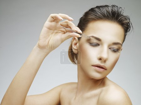 Photo for Beautiful young woman plucking eyebrows - Royalty Free Image