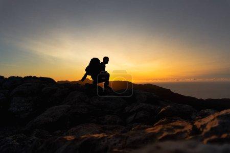Photo pour Randonneur au sommet d'une montagne accroupi et observant sur la crête de la montagne un beau coucher de soleil heure dorée avec une couleur intense et ciel bleu fusionné avec jaune, homme de profil regardant le soleil portant un grand sac à dos - image libre de droit