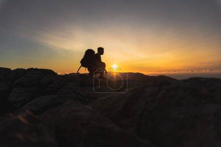 Photo pour Randonneur au sommet d'une montagne accroupi et observant sur la crête de la montagne un beau coucher de soleil d'heure dorée avec une couleur intense et ciel bleu fusionné avec jaune, homme de profil regardant vers la droite porte un grand sac à dos - image libre de droit