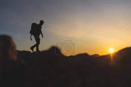 Photo pour Randonneur au sommet d'une montagne marchant sur la crête de la montagne avec un magnifique coucher de soleil doré avec une couleur intense et un ciel bleu fusionné avec du jaune, portant un grand sac à dos - image libre de droit