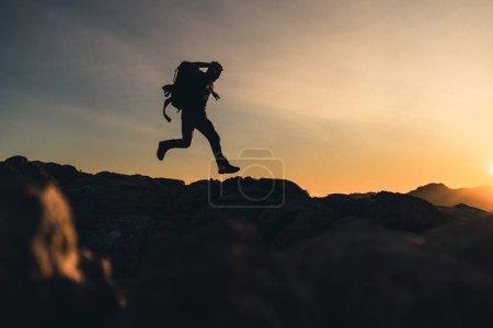 Photo pour Randonneur au sommet d'une montagne Courir sur la crête de la montagne avec un beau coucher de soleil doré heure avec une couleur intense et ciel bleu fusionné avec jaune, porte un grand sac à dos - image libre de droit