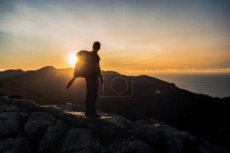 Photo pour Image horizontale du randonneur au sommet d'une montagne profitant du magnifique coucher de soleil de l'heure dorée avec une couleur intense et un ciel bleu fusionné avec du jaune, l'homme regarde le soleil et porte un grand sac à dos - image libre de droit