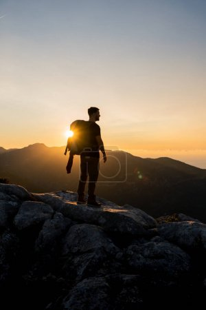 Photo pour Image verticale du randonneur au sommet d'une montagne profitant du magnifique coucher de soleil de l'heure dorée avec une couleur intense et un ciel bleu fusionné avec du jaune, portant un grand sac à dos - image libre de droit
