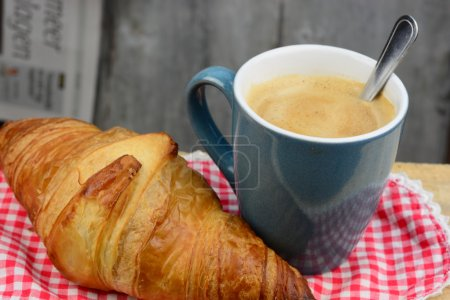 Blue coffe mug with fresh coffee and cream and croissant bread with a light grey blue tea towel with broidery on a old used wooden brakfast table in vintage style