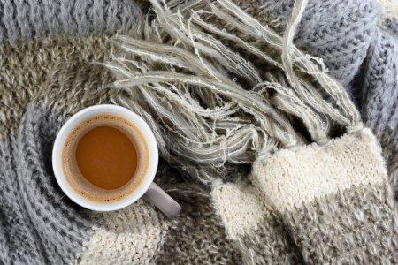 Photo pour Chocolat chaud dans une tasse à café avec une écharpe grise, ivoire, écru tricoté blanchi enroulé autour et barre de chocolat - image libre de droit