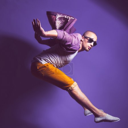 Young handsome male dancer in trendy glasses, purple jacket, whi