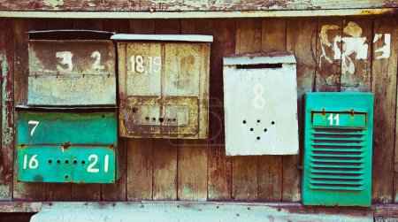 Photo for Old memory mailboxes concept. Multicolored old shabby mailboxes with numbers of people's memories houses over wooden scuffed background. Outdoor shot. Copy-space. - Royalty Free Image