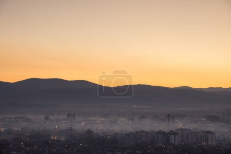 Photo for Soft, misty, hazy Pirot cityscape during night at autumn, distant horizon mountains and colorful golden and blue sky - Royalty Free Image