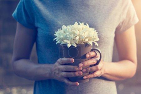 Photo pour Les mains de la femme tenant des fleurs blanches dans une tasse sur fond de fleurs tombantes, Filtrer l'image - image libre de droit