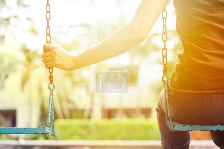 Photo for Lonely woman missing her boyfriend while swinging in the park of villa - Royalty Free Image