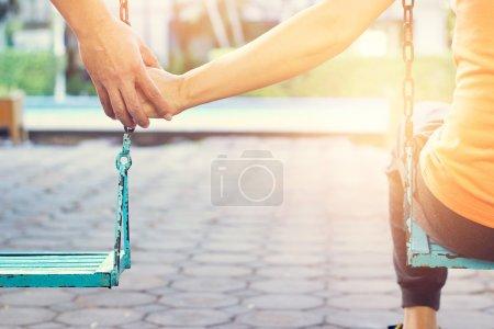 Photo pour Une femme qui se sent mal de solitude. Maintenant, elle est heureuse de venir de son petit ami. pendant qu'elle se balance, son petit ami est à côté, lui touchant la main et prenant soin d'elle dans le parc de la villa le matin . - image libre de droit