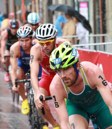 Photo for STOCKHOLM - AUG 23, Dan Wilson (AUS) and a lot of competitors chasing him in the rain during the triathlon race Mens triathloin the lead of the triathlon race Mens triathlon ITU World Triathlon series event Aug 23, 2014 in Stockholm, Sweden - Royalty Free Image