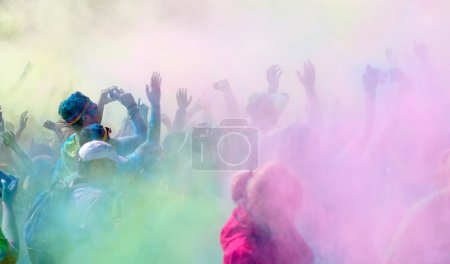 The pparticipants in the Color Run waiving the arms in the sky