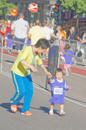 Very young asian girl and her mother running