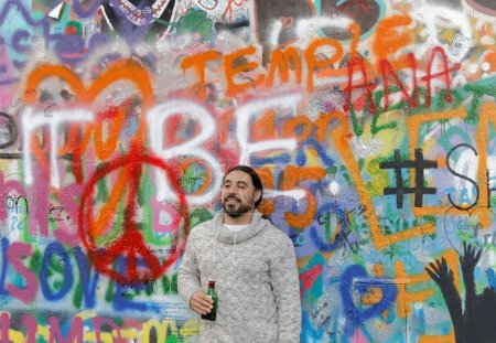 Man standing in front of colorful graffiti wall