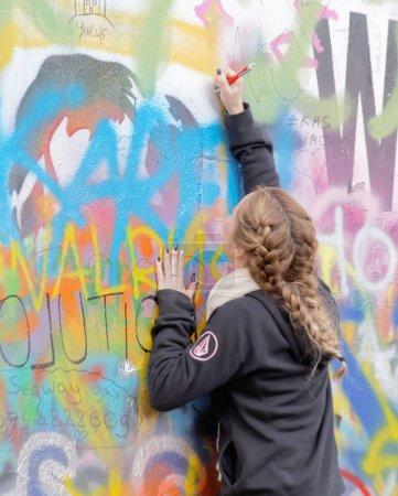 Woman writes on colorful graffiti wall