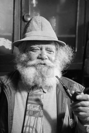 Photo pour Verticale d'un vieil homme avec une longue barbe fumant une pipe - image libre de droit