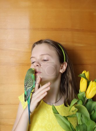 Young girl with green bird (little parrot) and yellow flowers