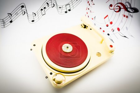 composition with vintage red record player and musical notes