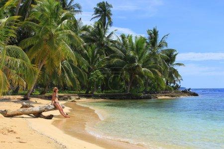 "Young beautiful woman enjoying her time and resting close to the sea in the southern beach of ""Pelicano"" Island, close to Yandup Island lodge, San Blas, Panama"