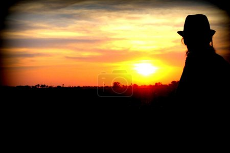 Relaxed young woman amazed in front of a wonderful sunset in Okavango Delta, Botswana