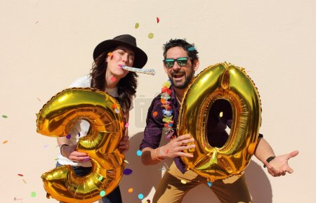 Cheerful couple celebrates a thirty years birthday with big golden balloons and colorful little pieces of paper in the air.